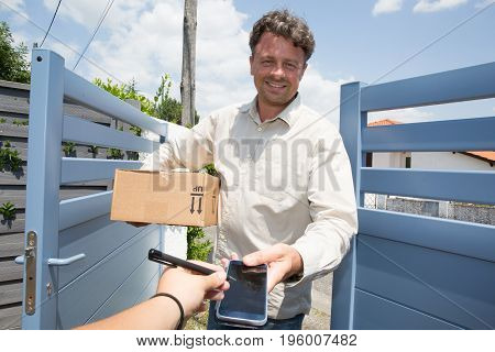 Woman Receiving A Parcel From A Delivery Guy