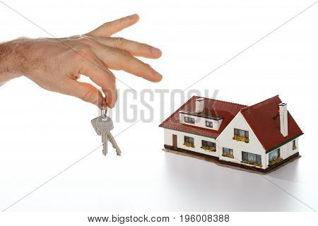hands are holding a key with house model in background