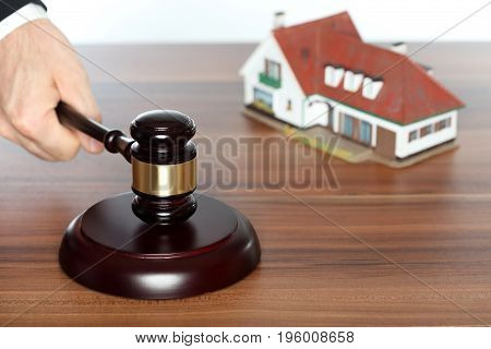 auction symbol with gavel in hand and house in background