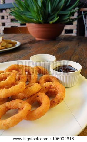 white plate with Homemade Crunchy Fried Onion Rings and sauces on wooden table background