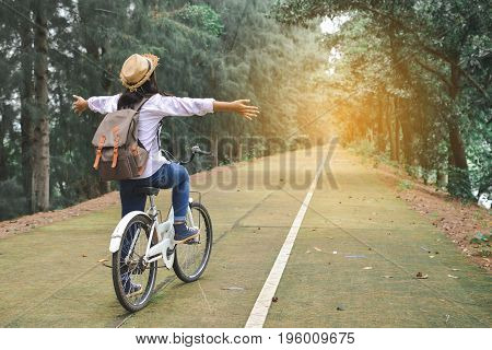 Happy women backpacker with white bicycle in nature background Relax time on holiday concept travel color of hipster style selective and soft focus
