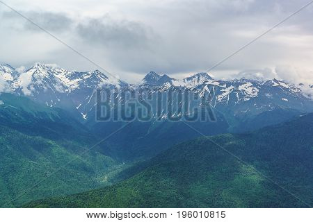 Snow-capped Peaks Of The Caucasus Mountains At Cloudy Summer Day
