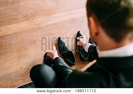 Business man tying shoe laces on the wooden floor. Groom getting ready in the morning before the wedding. Close-up. Top view