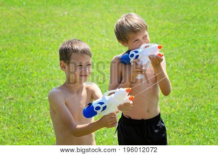Kids playing with water guns at hot summer day