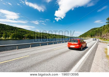 Red car on country road in Norway Europe Scandinavia. Auto travel on sunny day. Blue sky with clouds.