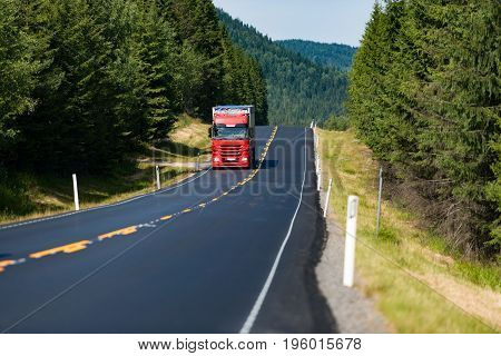 Red truck on country road in Norway Europe Scandinavia. Transportation on sunny day. Blue sky with clouds.