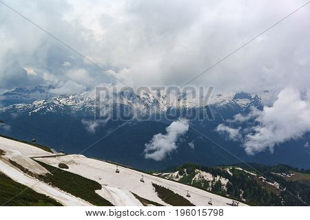 Panorama From The Snowy Mountaintops In The Clouds And Hillside, Equipped With Cable Cars In The For