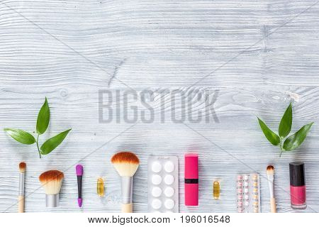 Contents of wonam's beauty bag. Cosmetics, contraceptives and pills on wooden table background top view.