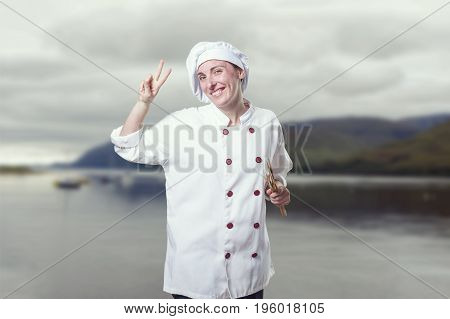 Nice Young Woman Chef Making Victory Gesture.