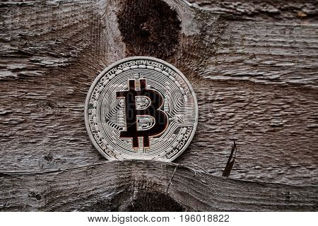 Digital currency physical silver bitcoin coin on the wooden background.