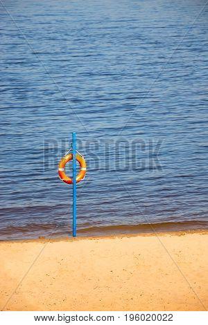 Orange Lifebuoy hanging near water, river or sea