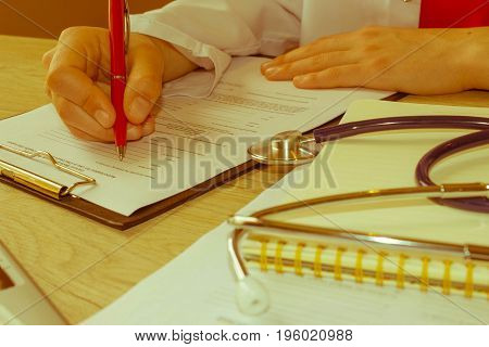 Doctor working in hospital writing a prescription. Healthcare and medical concept. Medicine doctor's working table - Retro color