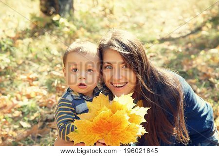 outdoor portrait of a young mother with her baby. Mom and son in an autumn park