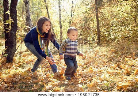 outdoor portrait of a young mother with her baby. Mom and son in the autumn park