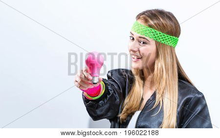 Woman in 1980's fashion holding a light bulb on a white background