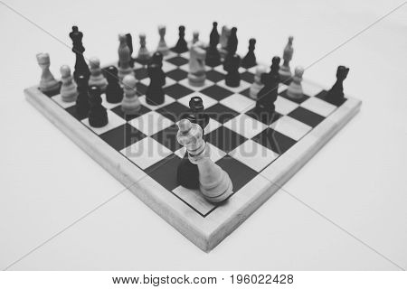 Missing King Replaced, chess pieces scatter a board, rival king and queen share a space