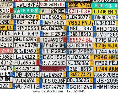 Odessa Ukraine - circa 2017: License numbers auto from all over the world on display. Discontinued license plate of cars from Europe car on the old wall. Background of old vintage antique car license plates of Europe.
