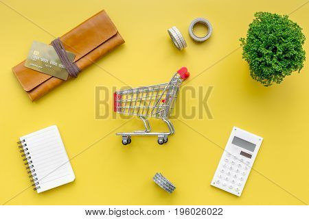 Shopping in online store. Bank card nearby purse, calculator and shopping cart on yellow background top view.