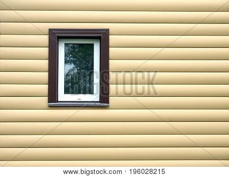 Building wall finished with beige siding panels with small vertical plastic window protect house from bad weather conditions horizontal photo front view