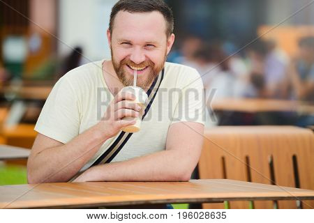 Happy Man With A Beard Drinking A Soft Drink In The City Smiling, Cold Coffee.