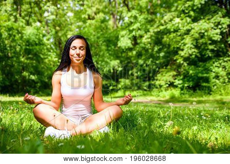 A beautiful young sporty girl sitting and meditating on the grass in the woods wearing a top and a shorts