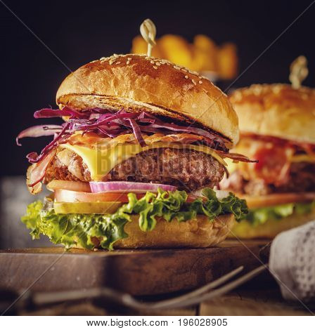 Delicious Fresh Burger With Meat, Bacon, Cheese And Vegetables On A Wooden Board, In A Rustic Soul S