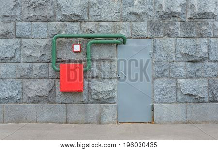 Wall with a gray door and a red metal box with fire hydrant pipes