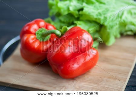Vegetables lie on a chopping wooden board on a roustic table - salad and red sweet pepper. Close up photo