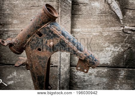 Rusty bicycle frame on a wooden background