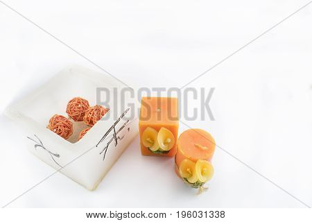 Candles and wicker balls in orange tones on a white background.