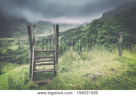 Wooden Ladder Over Fence Crossing with Spectacular View over Misty Valley in Snowdonia National Park