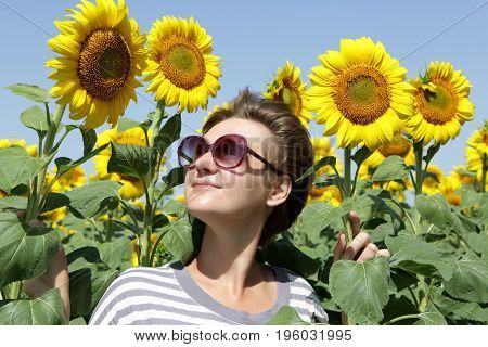 Woman Looking At Sunflowers
