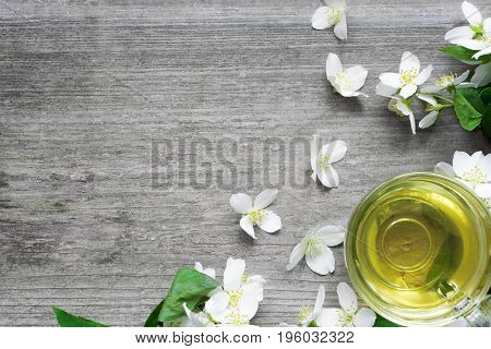 cup of green jasmine tea and Jasmine flowers on rustic wooden background with copy space. top view