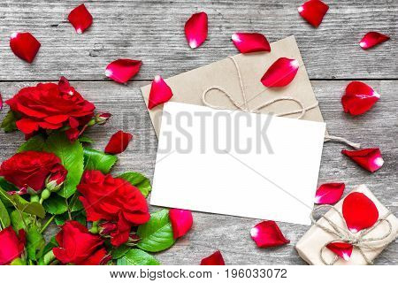 blank white greeting card and envelope with red roses flowers petals and gift box over rustic wooden table. mock up. top view
