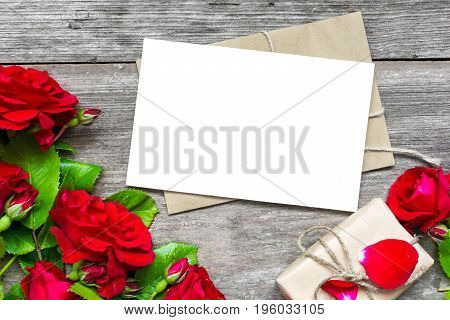 Bouquet of red roses with a blank greeting card and envelope with gift box on rustic wooden background with copy space. top view. mock up