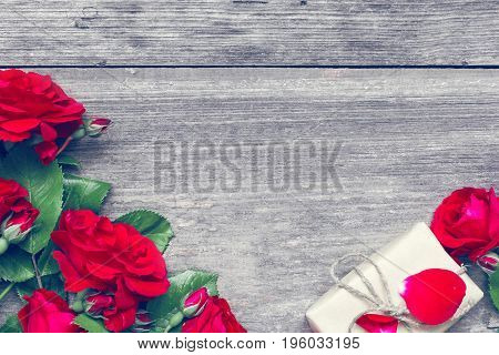 Bouquet of red roses and gift box on rustic wooden background with copy space. top view. mock up. vintage toning