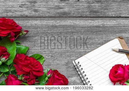red roses flowers and blank lined notebook to put your text on rustic wooden background with copy space. top view. mock up