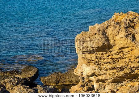 isolated big stones of the coast on an indistinct background of the blue sea