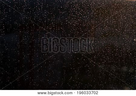 Rain drops on glass on the dark background. Close up view