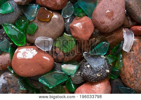 Glass beach. Natural texture with polished sea glass stones and sand. baltic sea. top view