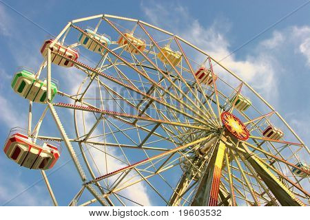 ferris wheel with blue sky with clouds in background