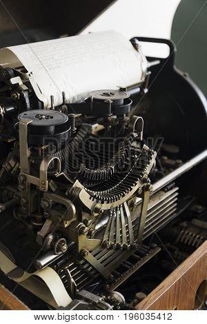Detail of an antique typewriter build in wooden box