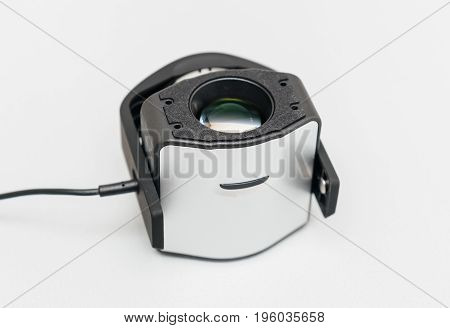 Open professional calibration device for modern monitor on light gray background. A Tristimulus colorimeter colloquially shortened to colorimeter is used in digital imaging to profile and calibrate output devices