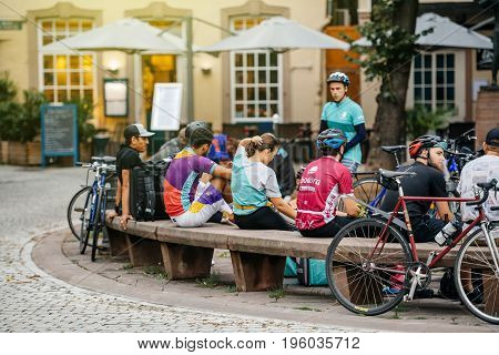 STRASBOURG FRANCE - JUL 12 2017: Deliveroo Foodora and Uber Eats employees resting near their bikes eating lunch in city center ready to deliver on time the food to the client.