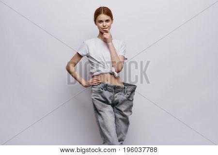 Young beautiful woman on a light background, weight loss, diet.port, progress, success.