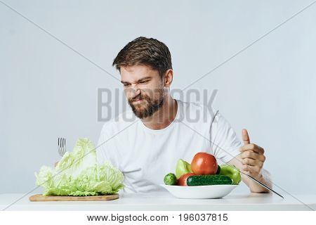 Young guy with beard on white isolated background, vegetables, vegan, healthy eating right.