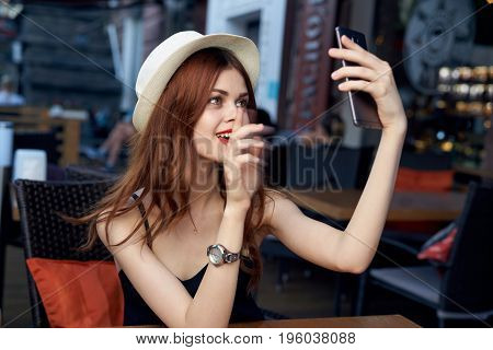 Young beautiful woman doing selfie on phone in cafe.