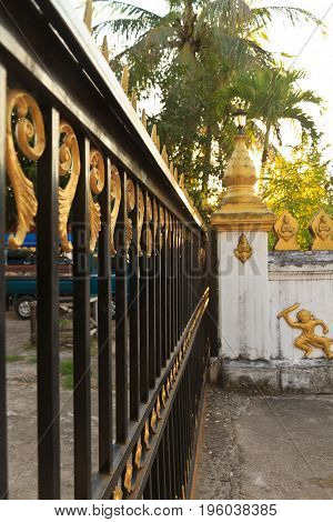 Gold and black wrought iron gate in Laos
