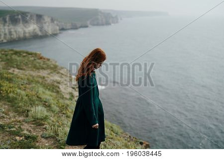 Young beautiful woman on a cliff of a mountain near the sea.