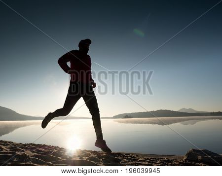Tall Fit Man Running Fast By The Sea On The Beach. Powerful Runner Training Outdoor In Summer Mornin